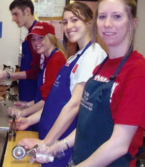 A picture of four Dietetic and Nutrition Club members doing service in a kitchen.