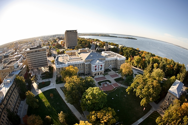 Bascom Hall atop Bascom Hill is pictured in a fisheye-lens aerial view of the University of Wisconsin-Madison campus during an autumn sunset on Oct. 5, 2011. Other majority campus facilities include, clockwise from lower left, Birge Hall, Van Vleck Hall, and Van Hise Hall. In the background at right is Lake Mendota and Picnic Point. The photograph was made from a helicopter looking west. (Photo by Jeff Miller/UW-Madison)